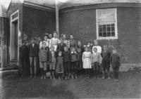 Portrait of students and teachers in front of the Brookline Round Schoolhouse
