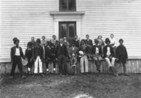 Portrait of actors in blackface and band members in front of a clabbered building in East Dover, Vt.
