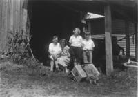 Family portrait in front of a barn with a porcupine skin