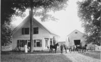 Man standing on a horse's back, with other horses and people, in front of farm in Windham County,Vermont