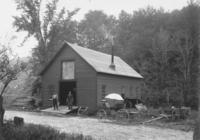Exterior of a blcaksmith's shop with two employees, Jacksonville, Vt.
