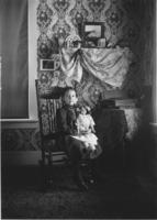 Young girl with doll inside house