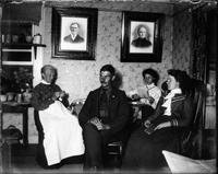 Family seated insde a house reading and knitting.