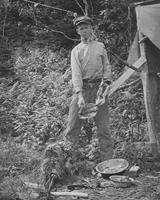 Caretaker on Couching Lion (Camel's Hump) preparing to cook a porcupine