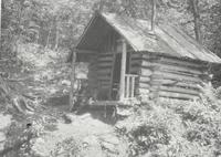 Man at small log cabin