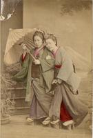 Two women posing in front of a mural of Mt Fuji