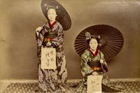 Two women posing for a picture with their calligraphy