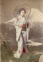Woman with umbrella posing in front of a mural of Mt Fuji