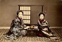 Two women posing with a tea set